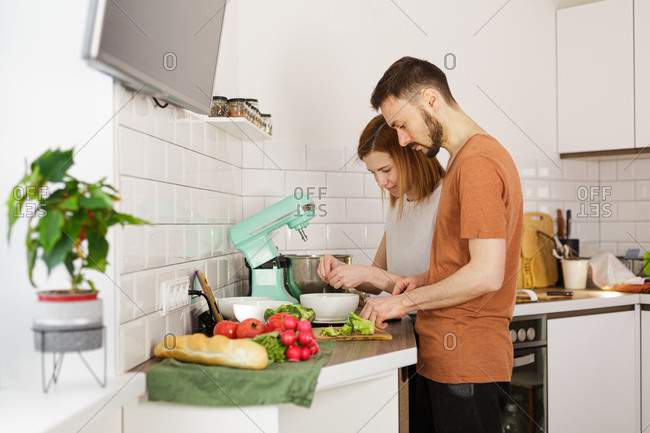 Couple preparing recipe in kitchen while looking at tablet