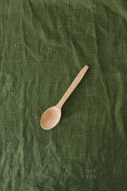 A wooden spoon on green cloth