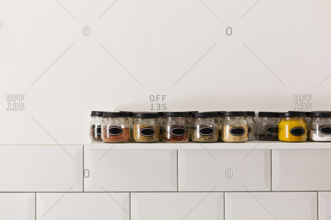 Glass jars filled with spices on a white shelf in kitchen