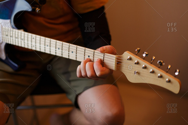 Close up of young man practicing his electric guitar
