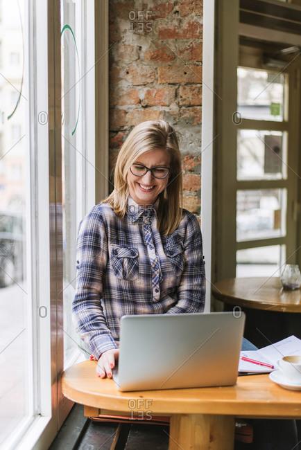 Blonde woman sitting in coffee shop using laptop