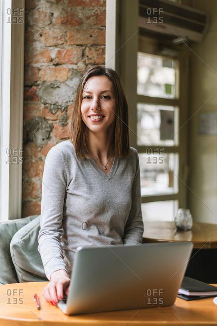 Brunette woman sitting in coffee shop using laptop