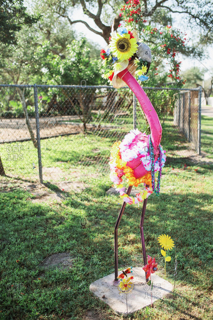 A flamingo yard decoration dressed up with flowers and beads