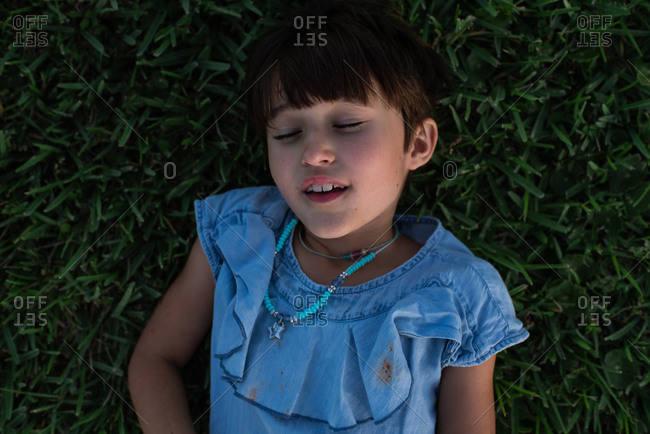 Portrait of a young girl lying in the grass with her eyes closed
