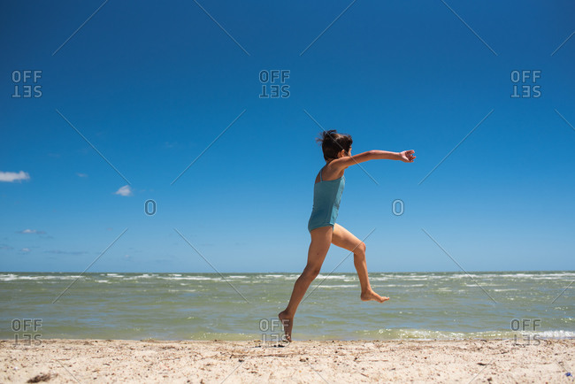 Young girl wearing blue swimsuit running on a beach