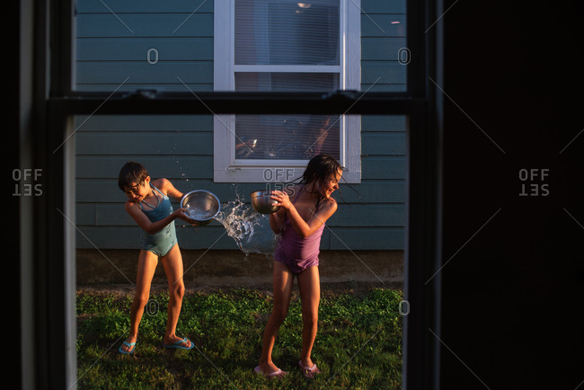 Two young girls throwing bowls of water on each other in the summertime