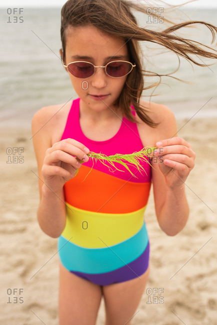 Young girl wearing colorful swimsuit holding seaweed on a beach