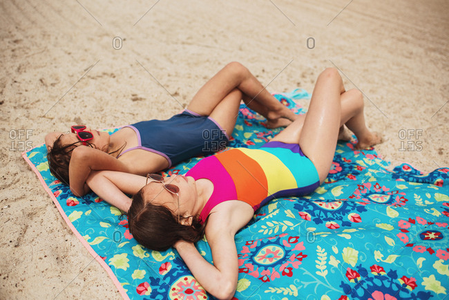 Two young girls sunbathing on a beach
