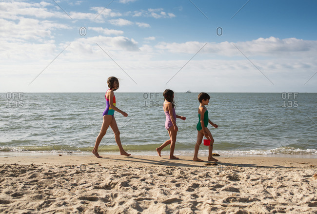 Three young girls walking on the seashore