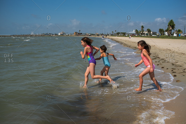 Three young girls running into the ocean