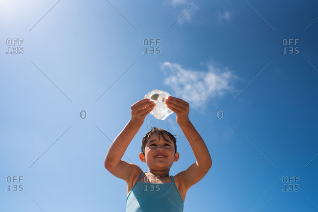 Low angle view of young girl wearing blue swimsuit on a sunny beach