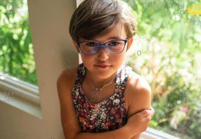 Portrait of a young girl with short hair and blue glasses crossing her arms