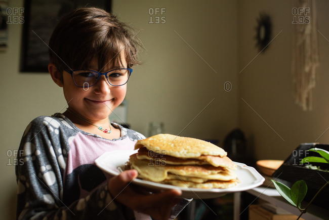 Young girl with short hair and blue glasses holding a plate with pancakes