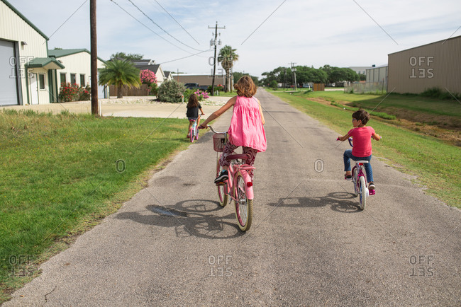 Three young girls riding bikes in the street