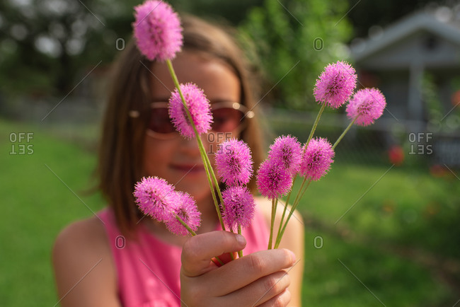 Girl holding pink flowers on a sunny day
