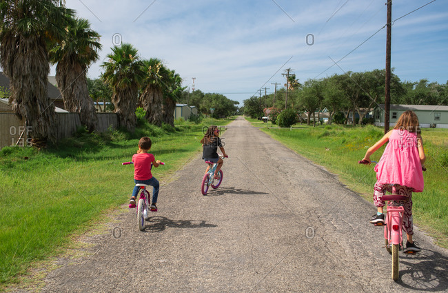 Rear view of three young girls riding bikes in the street
