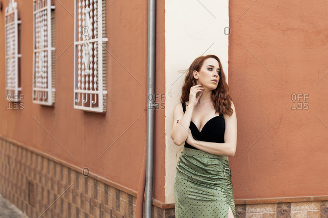 Thoughtful redheaded woman on a colorful street wearing a typical Spanish skirt in Granada, Andalusia, Spain