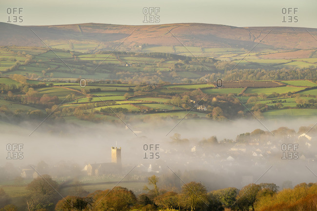 Misty winter morning view towards the church and Dartmoor village of Moretonhampstead, Devon, England, United Kingdom, Europe
