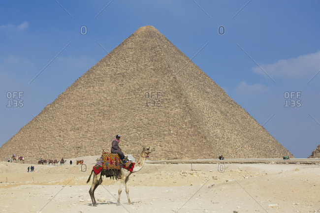 March 1, 2020: Rider and his Camel, Cheops (Khufu) Pyramid in background, Great Pyramids of Giza, UNESCO World Heritage Site, Giza, Egypt, North Africa, Africa