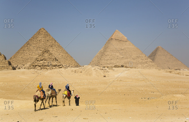 March 4, 2020: Tourists riding camels, Great Pyramids of Giza, UNESCO World Heritage Site, Giza, Egypt, North Africa, Africa