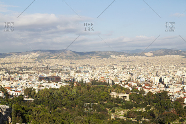 December 9, 2019: Temple of Hephaestus among trees on the ancient agora, in front of buildings of modern Athens, Greece, Europe