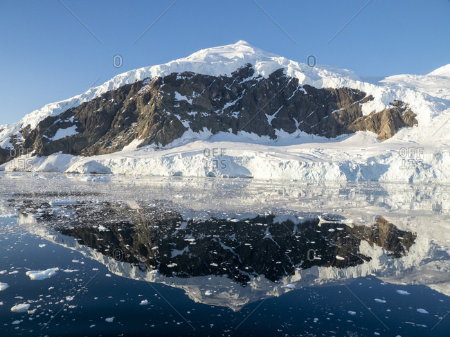 Ice-capped mountains reflected in the calm waters of Neko Harbor, Antarctica, Polar Regions