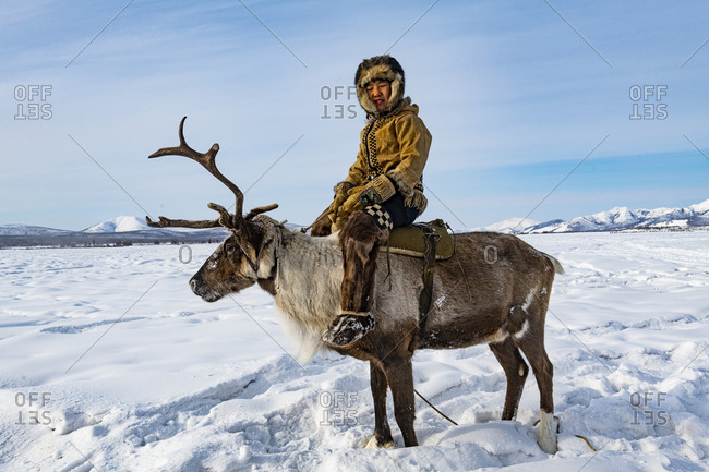 Evenk boy sitting on a reindeer, Oymyakon, Sakha Republic (Yakutia), Russia, Eurasia