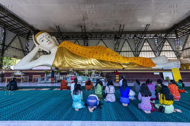 January 6, 2020: Pilgrims praying before a reclining Buddha, Su Taung Pyi pagoda, Myitkyina, Kachin state, Myanmar (Burma), Asia