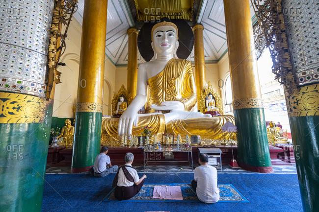 February 12, 2020: Pilgrims praying in the Shwedagon pagoda, Yangon (Rangoon), Myanmar (Burma), Asia