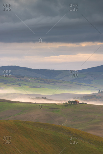 December 7, 2019: Rolling landscape with farm house and mist, Tuscany, Italy, Europe
