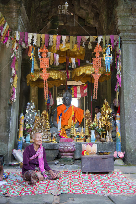 November 18, 2014: A woman sits crossed legged in prayer at the Angkor archaeological complex, Siem Reap, Cambodia, Indochina, Southeast Asia, Asia