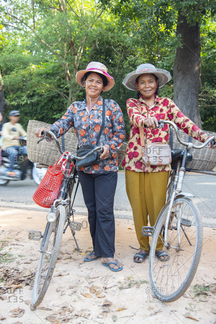 November 20, 2014: Two local women with their bicycles smiling together in Siem Reap, Cambodia, Indochina, Southeast Asia, Asia