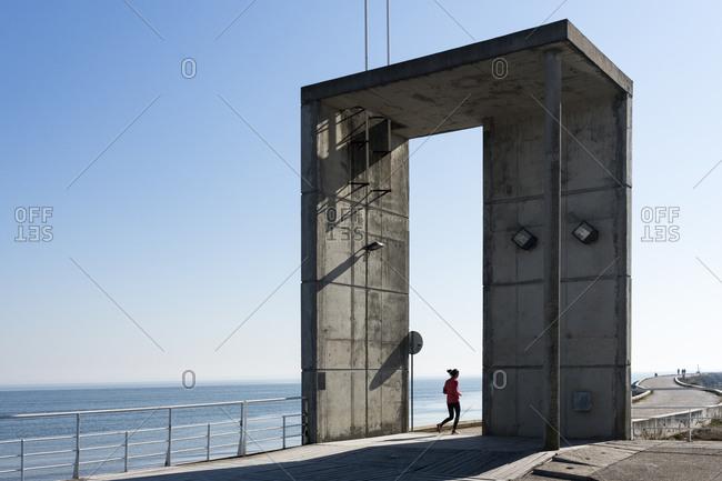 Female runner jogging along the Marina at Parque das Nacoes, Lisbon, Portugal, Europe