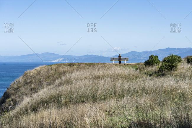 Woman on bench, Point Kean, Kaikoura, New Zealand