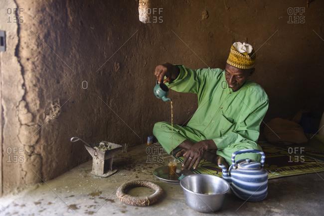 December 11,  2015: A Fulani man preparing tea, in a village of the Sahel, Burkina Faso