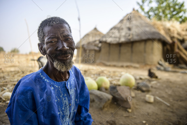 December 10,  2015: A Burkinabe man in his village, cutting pumpkins to turn them into drinking and eating containers, Burkina Faso
