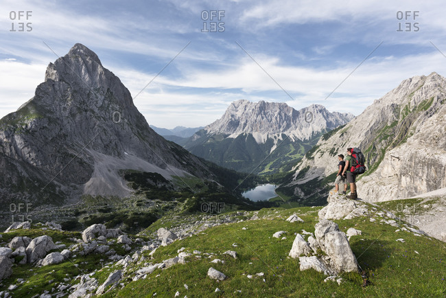 Hiker overlooking the Seebensee with Zugspitze and Sonnenspitze, Wetterstein Mountains, Alps, Tyrol, Austria, Europe