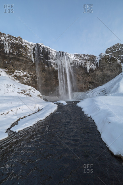 Seljalandsfoss Waterfall and snow covered banks in Iceland