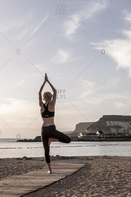 Woman practicing yoga, Amadores, Gran Canaria, Spain