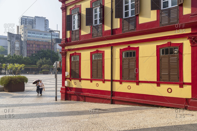 China - October 1, 2019: Women walking past Central Library on Tap Seac Square Macau, China