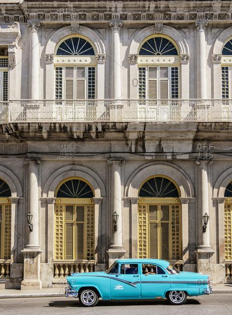 Cuba - March 23, 2019: Vintage car passing in front of Casino Espanol, Libertad Square, Matanzas, Matanzas Province, Cuba