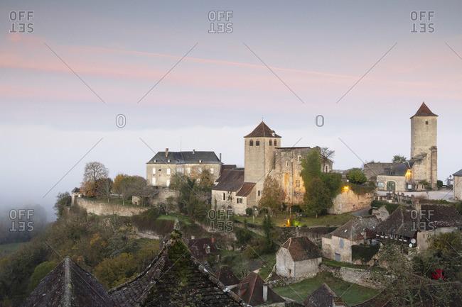 France, Midi-Pyrenees, Lot, Montvalent village illuminated before sunrise