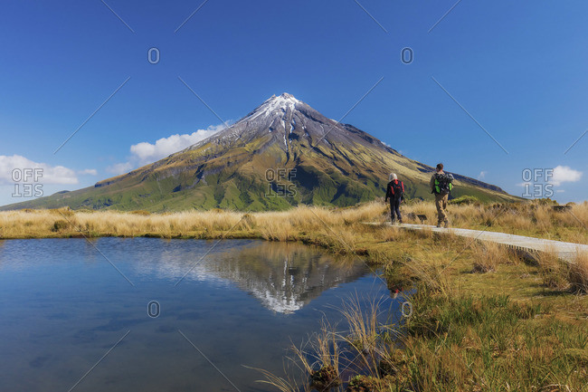 Two tourists hiking at Taranaki volcano in New Zealand northern island reflecting in a mountain pond on a sunny day