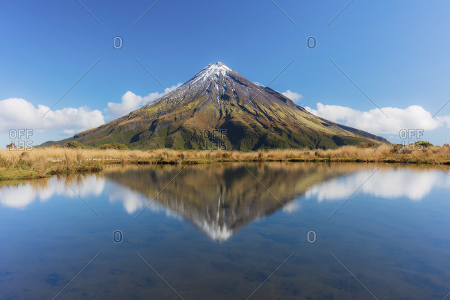 View of the Taranaki volcano in New Zealand northern island reflecting in a mountain pond on a sunny day