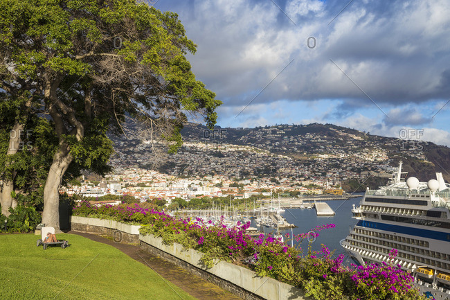 Portugal - November 12, 2019: Portugal, Madeira, Funchal, Lady sunbathing in hotel garden with Cruise ship nearby