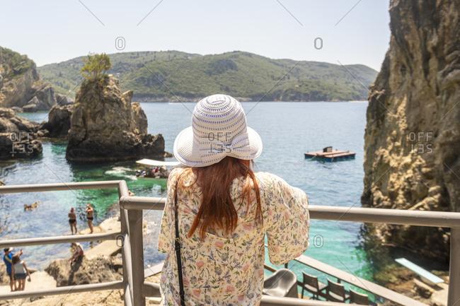 Tourist relaxing by La Grotta Beach with rock formations in Paleokastritsa, Corfu, Kerkira, Greece