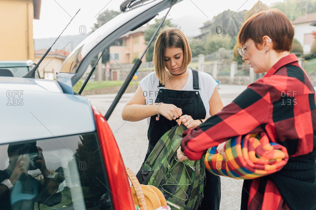 Friends getting picnic from car, Rezzago, Lombardy, Italy