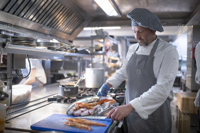 Chef preparing seafood dish in Italian restaurant kitchen