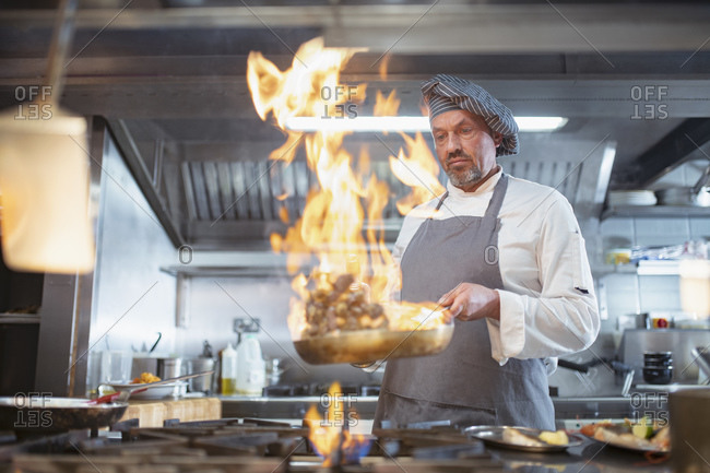 Chef cooking with brandy (flambe) and flames in Italian restaurant kitchen
