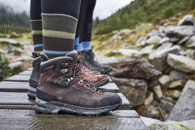 Female hikers standing on wooden footbridge, cropped view of ankles and hiking boots